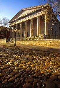 A color photograph of the Second Bank of the United States, a Greek Revival building resembling a temple with a cobblestone road in front of it.