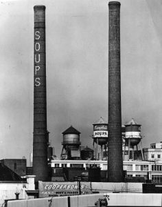 "A black and white photograph of two smokestacks and a cluster of water towers. The smokestacks have large letters reading ""Soups"" and the water towers are painted to look like Campbell's Soup cans."
