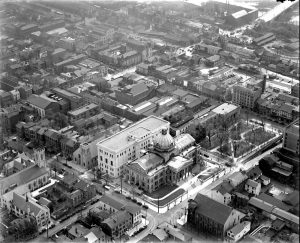 A black and white aerial photograph of downtown Norristown in 1930. The montgomery county court house, a greek revival building with a central dome, is prominently featured.