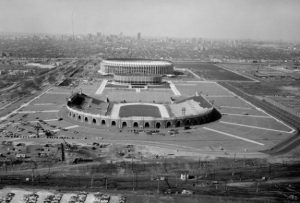 A black and white photograph of the old Philadelphia Sports Complex taken from the East. Photo shows JFK Stadium, The Spectrum Arena, and Veterans Stadium in a row, surrounded by empty parking lots.