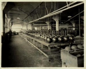 A black and white photograph of steel helmets being made on the assembly line of the Ford Automotive factory in 1917