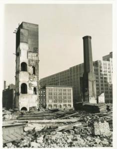A black and white photograph of a factory being demolished