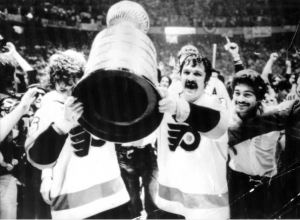 A black and white photograph of Bobby Clarke and Bernie Parent holding the Stanley Cup while a crowd cheers behind them.