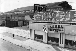 A black and white photograph of a dilapidated ice rink with peeling paint. Marquee on the front reads