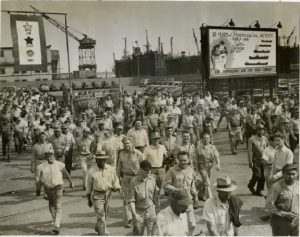 "A photograph of a crowd of a mixed group of black and white men in work clothes leaving Sun Ship's complex in Chester circa 1950. Behind them a sign reads ""30 years of progressive activity"""