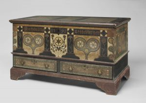 "A color photograph of a black chest with colorful painted heart and flower motifs. The name ""Magdalena Leabelsperger"" and the year 1792 are painted on the top."