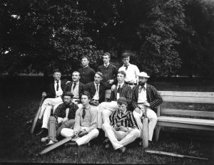 A black and white photograph of eleven cricket players, most wearing striped uniforms, posing on a lawn. Several hold cricket bats or balls and one wears protective pads on his shins and knees.