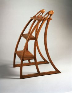A color photograph of a curved wooden step ladder. The tops of the hand rails are carved into a stylized donkey and elephant.