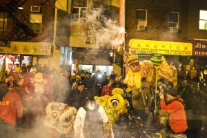 a color photograph of a lion dance in Chinatown showing dancers wielding large chinese lion puppets and smoke clouds from firecrackers