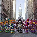 A photograph of mummers -- men dressed in elaborate, colorful costumes -- walking down Broad Street with City Hall in the background