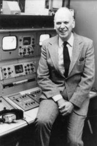 Black and white photograph of Professor John Roberts leaning on studio recording equipment.