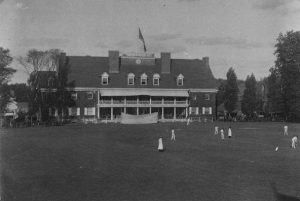 a black and white photograph of a group of golfers on the lawn of the Germantown Cricket Club with the clubhouse in the background.