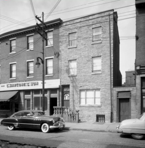 "a black and white photograph of a three-story brick building with a sign reading ""Sarcone & Son"" on the front"