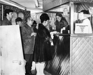 A black and white photograph of a line of people wating to buy lottery tickets from the newly formed Pennsylvania Lottery.