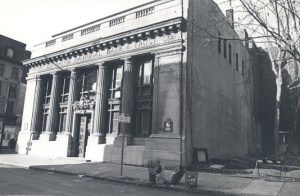 a black and white photograph of a bank built in the classical style with prominent front columns