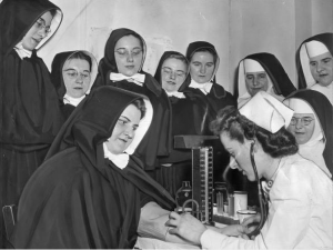a black and white photograph of a nurse drawing blood from a nun while several other nuns and postulants look on