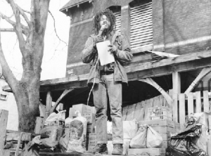 a black and white photograph of Delbert Africa speaking into a microphone in front of his home, with a pile of foodstuffs around his feet