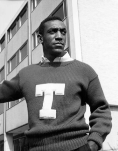 a black and white photograph of Bill Cosby in a Temple University sweater