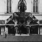 a black and white photograph of the Trocadero Theater in 1917 draped in American Flags