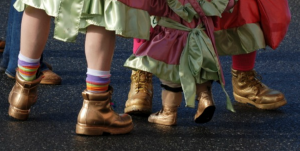 close up photograph of mummer's feet, from the shin down. Pieces of colorful costumes flow over work boots that have been spray painted gold