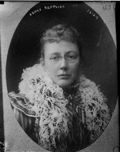 A black and white photograph of Agnes Repplier. She wears an ostrich feather boa and metal framed eyeglasses.