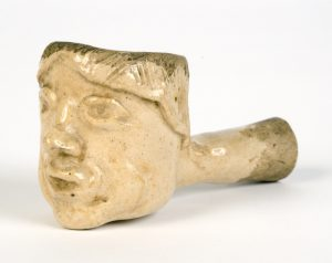 a color photograph of a pipe sculpted in the image of a man's face