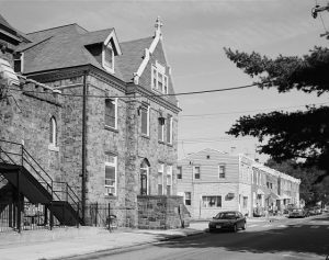 a black and white photograph of a three story stone convent with a cross topping the front-facing roof gable. A set of prominent stone stairs leads to the first floor entrance.