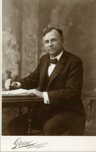 a black and white photograph of John Wanamaker in a suit seated at a desk. He faces the camera, and in his right hand holds a pen as if writing.