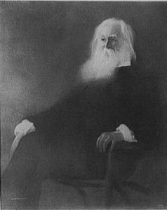 a black and white photograph of Walt Whitman as an elderly man. He sits in a chair with legs crossed.