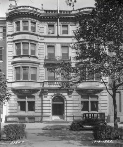 a black and white photograph of the Rittenhouse Club Headquarters, a four story building with a flat roof, white limestone facade, and twin bay windows
