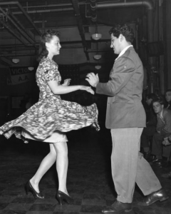 a black and white photograph of a couple performing the jitterbug. The woman has just executed a spin move and her skirt flares out from the movement.