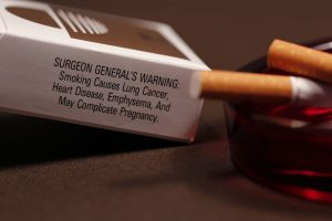 a color photograph of a pack of cigarettes focusing on the Surgeon General warning. An ashtray with two cigarette butts is in the foreground.