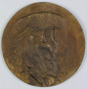 a color photograph of a medal with the likeness of Walt Whitman pressed into it