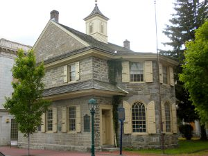 a color photograph of a two story Colonial building clad in stone.