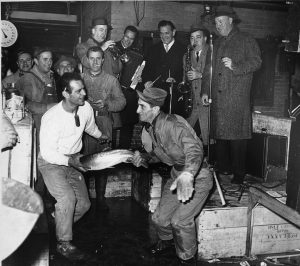 a black and white photograph of two men doing the twist while each holding one end of a large fish. In the background, a band plays.