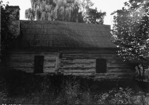 A black and white photograph of a small log cabin with wood shingle roof and stone chimney