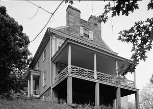 a black and white photograph of the Thomas Leiper estate. It features a prominent porch, columed entryway, and twin chimneys.