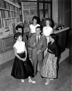 a black and white photograph of a small group of teenagers surrounding Dick Clark. Clark holds a microphone. Behind them is the set for American Bandstand.