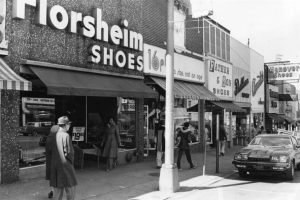 A black and white photograph of shoppers walking through a busy business district. Sign on shop reads Florsheim Shoes.