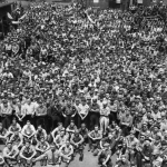 A black and white photograph of a crowd of thousands of men. The front row is seated while the rest stand.