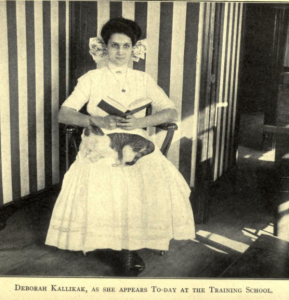 "A black and white photograph of Deborah Kallikak reading a book with a tabby cat on her lap. Text reads ""Deborah Kallikak, as she appears to-day at the Training School"""