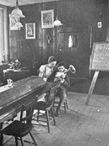 A black and white photograph of a room in the Elwyn Training School. A nurse sits with a small child on her lap. The child holds a small tuba-like musical instrument. In the background is a chalk board on an easel with musical notation hand written on it.