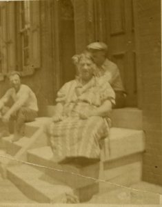 a black and white photograph of Maria Innocenza Procopio Siciliano and two unidentified men sitting on the stoop of a rowhouse
