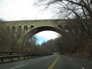 A color photograph of the Wissahickon Memorial Bridge, a two-ribbed, open-spandrel, reinforced concrete bridge.