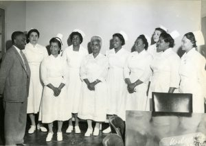 a black and white photograph of nine African-American women in white nursing uniforms and caps. An African-American man in a suit stands with them.