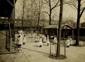 Small children in white uniforms play outside as nurses stand watching