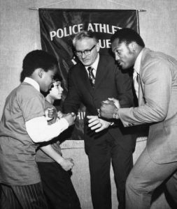 Joe Frazier poses with his fist raised opposite of PAL kids. In the background of the photograph is Police Commissioner Joseph O'Neill.