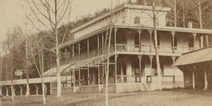 A nineteenth century photograph of the Maple Spring Hotel. The building is rectangular in shape with a pronounced porch along its exterior. Behind the building is a forest.