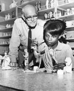 A black and white photograph of a Police Athletic League officer standing over the shoulder of a teenage woman, as she paints a ceramic sculpture.