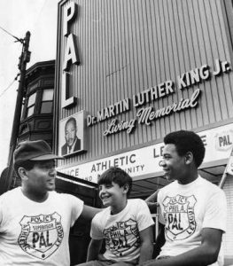 A PAL officer hangs out with two PAL children in front of a PAL building.